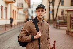 Stylish fashionable young man in a vintage fashion coat. In a cap with a black bag standing on the street in the city Royalty Free Stock Photos