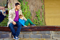 Stylish father and son on the bench, in front of old tree Stock Images