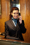 Stylish female attendant at hotel reception. Communicating on phone Stock Photo