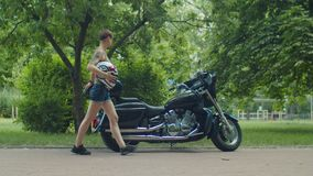 Stylish female biker with helmet ready for ride. Stylish charming female motorcycle rider with protective helmet in hand walking along parked motorbike before stock video