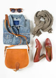 Stylish female clothes set. Woman/girl outfit on white background. Blue denim jacket, gray scarf, vintage crossbag, brown shoes an Royalty Free Stock Photography