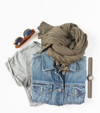 Stylish female clothes set. Woman/girl outfit on white background. Blue denim jacket, gray t-shirt, scarf, hand watch and retro su Stock Images