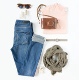 Stylish female clothes set. Woman/girl outfit on white background. Blue jeans, gray scarf, vintage camera, pink t-shirt, hand watc Stock Photos