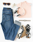Stylish female clothes set. Woman/girl outfit on white background. Blue jeans, pink t-shirt, stripe wedges, headphones, hand watch Royalty Free Stock Photos