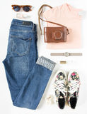 Stylish female clothes set. Woman/girl outfit on white background. Blue jeans, print sneakers, vintage camera, pink t-shirt, hand Royalty Free Stock Photo
