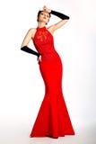 Stylish female in long red fashion dress posing Royalty Free Stock Photo