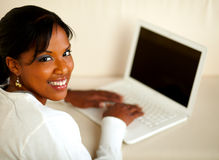Stylish female looking at you working on laptop Stock Photos