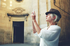 Stylish female tourist making photo of architectural monument during while touring in the city Royalty Free Stock Photo