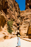 Stylish female tourist in trendy hat and sky-blue dress explore canyon Siq leading to The Treasury, Al Khazneh. Travel and adventu Royalty Free Stock Photography