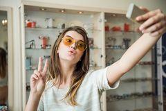 Stylish feminine young female student in optician store making glamorous face and showing v sign while taking selfie in. New pair of trendy sunglasses she Stock Photo