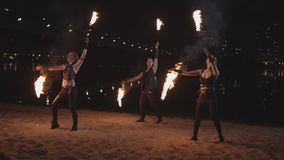 Artists performing dance with fire poi near river stock video