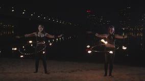 Pretty females twisting fire hula hoops at waist stock video