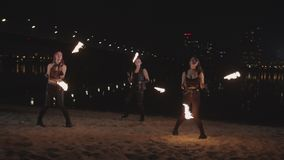 Stylish fireshow artists dancing with poi by river stock video footage