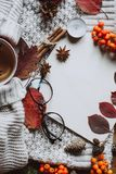 Stylish Flat lay view of autumn leaves and textured scarf on wooden background with cup . Autumn or Winter concept. stock photos