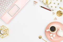 Stylish flatlay frame arrangement with pink laptop, coffee, milk holder, planner, glasses and other accessories. Feminine business mockup, copyspace, white stock photo
