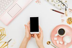Stylish flatlay frame arrangement with woman`s hands holding white smartphone with black copyspace, pink laptop, coffee, planner. And other accessories stock images