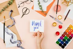 Free Stylish Flatlay With Art Supplies, Envelopes, Brushes, Watercolors, Glasses, Pen And Woman`s Hand Holding A Handmade Card Royalty Free Stock Image - 113000336
