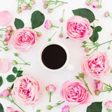Stylish floral composition made of pink roses, buds and mug of coffee on white background. Flat lay, Top view. Stylish floral composition made of pink roses Royalty Free Stock Images