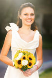 Stylish Fresh smiling bride in a white dress with a bouquet of s. Unflowers Stock Photo