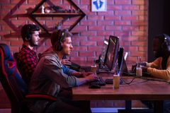 Stylish friends are resting together. Hobby of real men. Profile of concentrated young gamers are sitting in computer club and playing video games on computer Royalty Free Stock Images