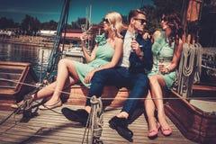 Stylish friends on a yacht. Stylish wealthy friends having fun on a luxury yacht Royalty Free Stock Photos