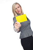 Stylish frowning woman holding up a yellow card. To the camera showing that a flagrant foul has been committed, isolated on white Stock Photography