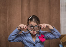stylish funny little girl looking toward trough the magnified glasses on brown curtains background inside the room Stock Photo