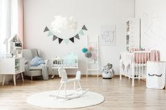 Stylish furniture in kid`s room. Stylish furniture in a monochromatic spacious kid`s room with tulle pompons as decoration stock photos