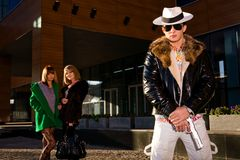 Stylish gangster with a gun and two young women. On background outdoors Royalty Free Stock Photo