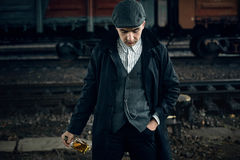 Stylish gangster man with bottle whiskey in retro look posing on Royalty Free Stock Photos