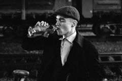 Stylish gangster man drinking. posing on background of railway. Royalty Free Stock Images