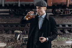 Stylish gangster man drinking. posing on background of railway. Stock Image