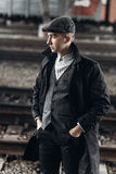 Stylish gangster man posing on background of railway. england in Stock Photo