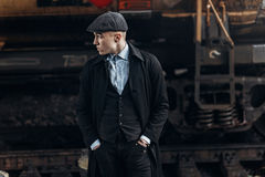Stylish gangster in retro outfit posing on background of railway Stock Image