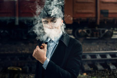 Stylish gangster smoking in tweed look, posing on background of Stock Photos