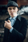 Stylish gangster smoking in tweed look, posing on background of Royalty Free Stock Photo