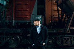Stylish gangster in tweed outfit posing on background of railway Royalty Free Stock Images