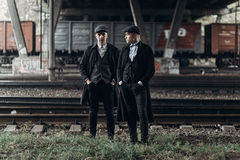 Stylish gangsters men, posing on background of railway. england in 1920s theme. fashionable brutal confident group. atmospheric  m. Oments. space for text Royalty Free Stock Photo