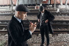 Stylish gangsters men, smoking pipe on background of railway. en Stock Photography