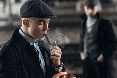 Stylish gangsters men, smoking pipe on background of railway. en Royalty Free Stock Images