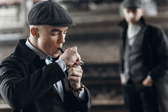 Stylish gangsters men, smoking pipe on background of railway. en Royalty Free Stock Photography