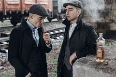 Stylish gangsters men, smoking. posing on background of railway Stock Photography