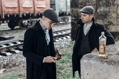 Stylish gangsters men, smoking. posing on background of railway Stock Image