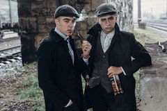 Stylish gangsters men, smoking. posing on background of railway Royalty Free Stock Images
