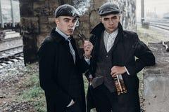 Stylish gangsters men, smoking. posing on background of railway Stock Photo