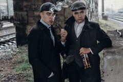 Stylish gangsters men, smoking. posing on background of railway Royalty Free Stock Photo