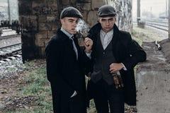 Stylish gangsters men, smoking. posing on background of railway Royalty Free Stock Photos
