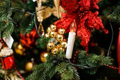 Stylish garland in the form of candles. On the background of fir tree decorated with toys Stock Photography