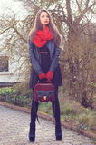 Stylish girl. Stylish beautiful girl posing outdoors in black leather jacker, red scarf and red gloves Royalty Free Stock Images