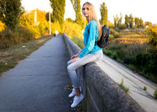 Stylish girl with a backpack sitting Royalty Free Stock Photos